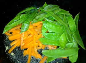 In the same skillet, add the carrots and snow peas.